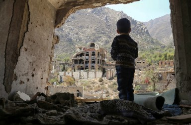 TOPSHOT - A photo taken on March 18, 2018, shows a Yemeni child looking out at buildings that were damaged in an air strike in the southern Yemeni city of Taez. / AFP PHOTO / Ahmad AL-BASHA        (Photo credit should read AHMAD AL-BASHA/AFP/Getty Images)