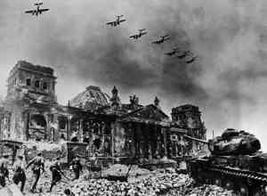 In this composite image by Yevgeny A. Khaldei (March 23, 1917 - October 6, 1997), the renowned photographer has seven Petlyakov Pe-2 dive bombers overflying the Reichstag while Red Army soldiers rush the building supported by a Josef Stalin IS-2 tank. There are at least four separate images in this composite. The Reichstag is one; the original has a destroyed bus in the lower left, which was covered by the onrushing Red Army squad. The squad is likely a staged reenactment, possibly taken on May 4 when photographer Ivan M. Shagin (1904-1982) also photographed the reenactment. The Petlyakov Pe-2 aircraft appear to be the same aircraft duplicated seven times. The IS-2 tank is significant, not only because it is named after Stalin; IS-2 tanks, attached as one heavy tank brigade to each of the Soviet Fronts (Army Group). Later enough IS-2s were produced so that each tank corps had an IS-2 regiment with twenty-one tanks. The IS-2 was reserved for storming fortifications, in concert with combat engineers. It could engage German Tiger I and II tanks, although the Tiger's 88mm (3.46 inch) gun could outrange the IS-2's 122mm (4.8 inch) gun. The composite photo was often used by Soviet photographers, who did not have any ethical issues with manipulating images. Khaldei himself made several other composite images during the war.